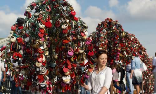 une femme au profil slave se tient près d'un arbre recouvert de cadenas à Moscou