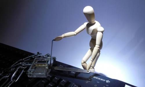 un bonhomme en bois tente d'ouvrir le cadenas qui enferme un clavier d'ordinateur