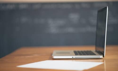 Un laptop posé devant un tableau noir dans une salle de cours