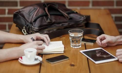Un table de café couverte d'outils de travail en mobilité (smartphone, laptop...)